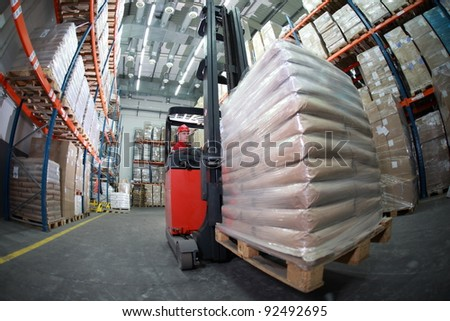 Forklift operator in red uniform and  helmet at work in warehouse - fish-eye lens