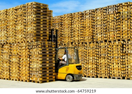 Forklift operator inside row of wooden euro pallets - stock photo