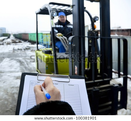 Forklift stands at the entrance to warehouse. Hand of woman makes a record delivery of goods - stock photo