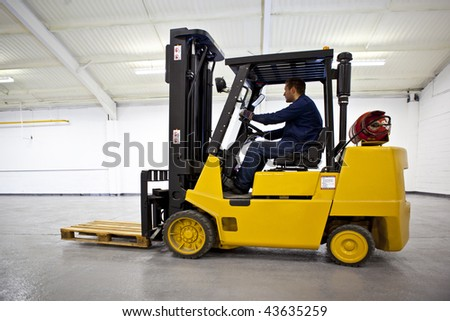 Forklift Truck in empty Warehouse with driver - stock photo