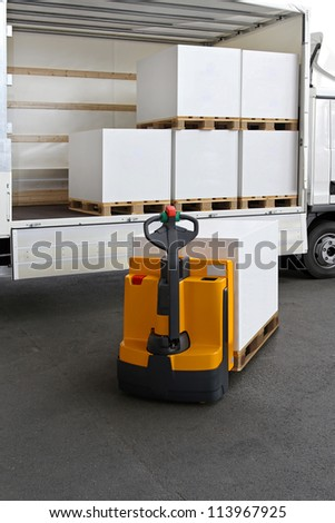 Forklift truck loading pallets of paper in lorry - stock photo