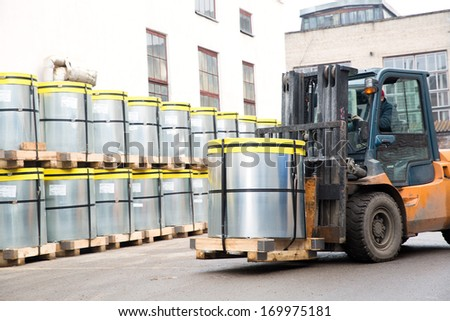 Forklift truck stacker transporting transformer steel roll cargo with pallet at factory warehouse - stock photo