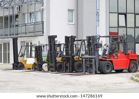 Forklift trucks in front of distribution warehouse