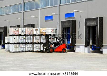 Forklift vehicle in front of cargo doors at industrial warehouse