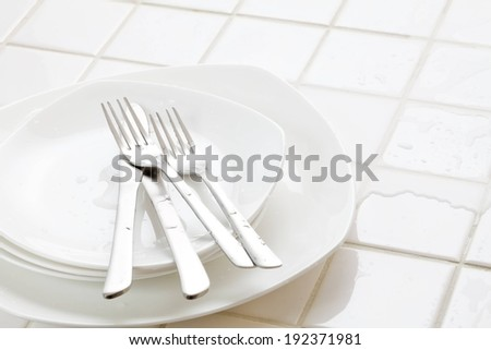 Forks and knives on a stack of dishes. - stock photo