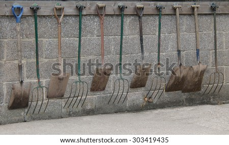 Forks and Spades for Mucking Out Horse Stables. - stock photo