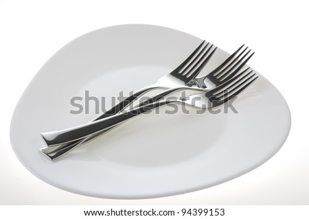 Forks on a plate isolated over white background