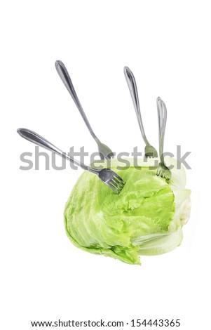 Forks on Iceberg Lettuce on White Background - stock photo