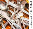 Forks, spoons, knives and  dishware washed under a stream of water - stock photo