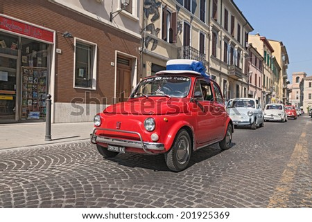 """FORLI', ITALY - JUNE 8: unidentified driver on a red vintage Fiat 500 with a funny hat, lead a line of the classic italian mini car during the rally """"Emozioni 500""""  on June 8, 2014 in Forli', italy  - stock photo"""