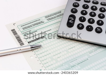 Form of income tax return with ball pen and pocket calculator - stock photo