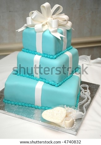 Formal birthday cake on table with necklace and heart-shaped box - stock photo