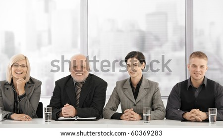 Formal businessteam portrait of different generations sitting at meeting table, smiling at camera.? - stock photo