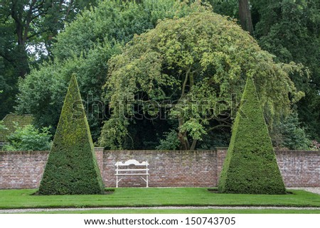 Formal castle garden in Amerongen Holland with pillarts of buxus and a bench