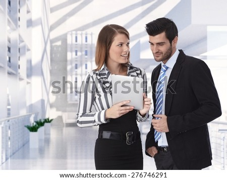 Formal clothed business partners holding tablet discussing at office, smiling. - stock photo