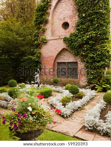 Formal flower beds in front of old brick building with statue - stock photo