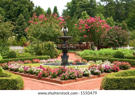 Formal garden with fountain in center and bright flowers *web use*
