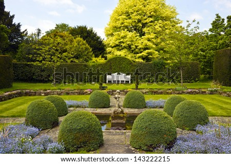 Formal garden with white wooden bench and topiary shrubs. - stock photo