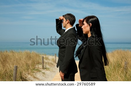 Formal man and woman as investmentteam standing on the sunny beach - stock photo