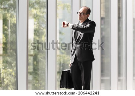 Formal wear Businessman with briefcase looking at his watch - stock photo
