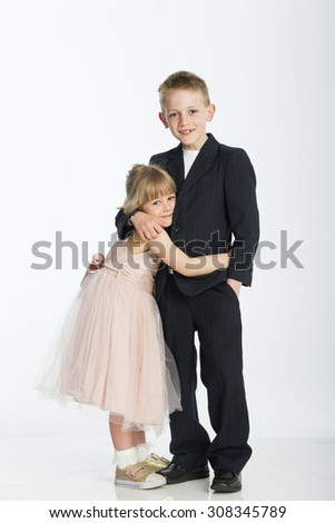 Formally dressed brother and sister. They are hugging and smiling for the camera against a white background - stock photo