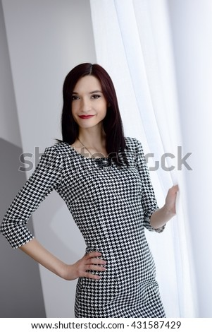 Formally dressed young brunette woman near window - stock photo