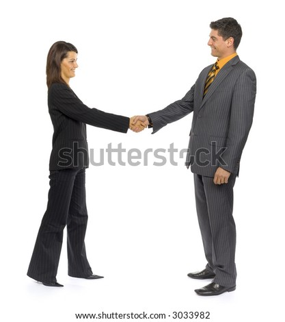 Formalwear man and woman are standing and looking their faces. They're handshaking. Side view.Whole bodies are visable. - stock photo