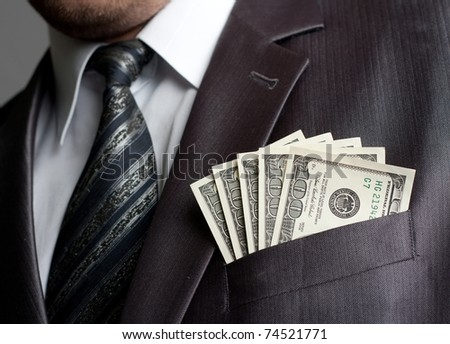 Formalweare businessman with earned money in suit pocket - stock photo