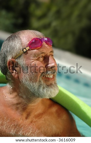 Former professional swimmer working out in the pool in his backyard - stock photo