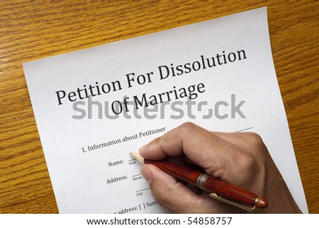 Forms for a divorce on a table, male hand with pen is starting to fill out the form - stock photo