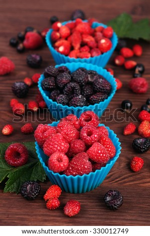 Forms for baking cakes filled with berries on the wooden background; raspberries in the foreground; blackberries and strawberries in the background; ingredients for baking; summer berry menu - stock photo