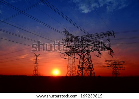 Forms of high voltage towers under the setting sun exposure   - stock photo