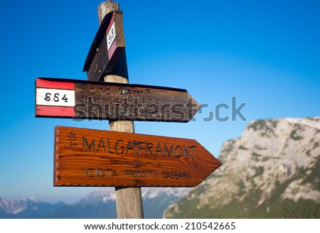 Foro Camp signs with blue sky and blurred mountains in the background, Dolomite, Italy