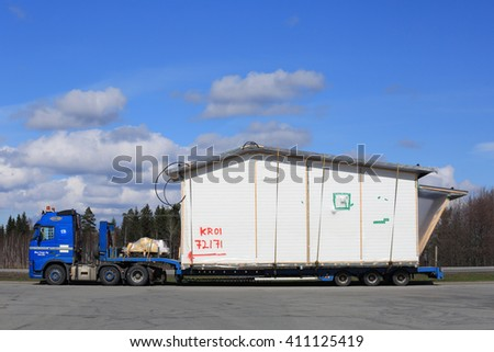 FORSSA, FINLAND - APRIL 23, 2016: Blue Volvo FH semi truck is to transport a prefabricated house module as oversize load in South of Finland. - stock photo