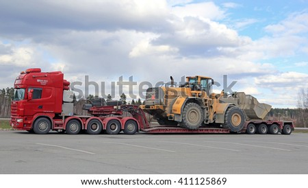 FORSSA, FINLAND - APRIL 23, 2016: Scania 164G truck stops at a truck stop during the oversized transport of heavy Volvo L350F wheel loader, side view.  - stock photo