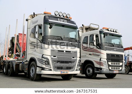 FORSSA, FINLAND - APRIL 6, 2015: Two modern Volvo FH logging trucks parked on a yard. The process of developing a new truck starts many years before it is launched. - stock photo