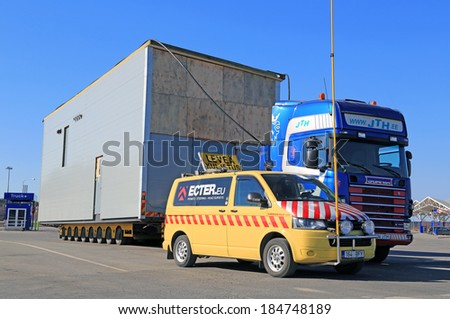 FORSSA, FINLAND - MARCH 29, 2014: Pilot car and a heating plant as an oversize load. On Finnish roads an escort car is necessary, if the load exceeds 3,5 m in width or 30 m in length.  - stock photo