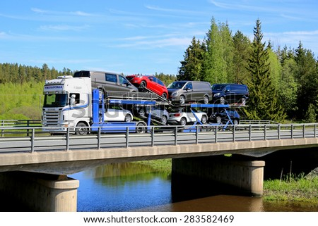 FORSSA, FINLAND - MAY 30, 2015: Scania R480 truck hauls a load of new cars along bridge. The Finnish automotive industry estimates that 109,000 new passenger cars will be sold in Finland in 2015. - stock photo