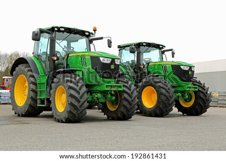 FORSSA, FINLAND - MAY 10, 2014: Two John Deere 6210R agricultural tractors on a yard. John Deere's Manure Sensing System is awarded in the technical innovation category at the FIMA 2014 show. - stock photo