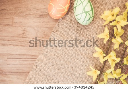 forsythia flowerd twig ans decorations on a natural wood and burlap surafce - copy space - stock photo
