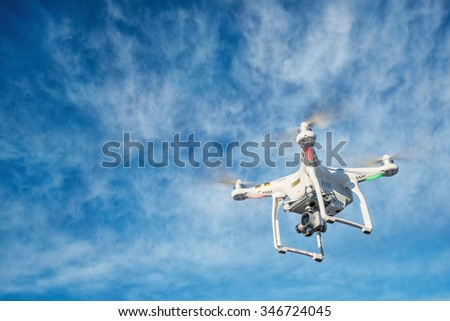 FORT COLLINS CO, USA, DECEMBER 2, 2015:  DJI Phantom 3 quadcopter  drone is flying with a 4K video camera against blue sky. - stock photo