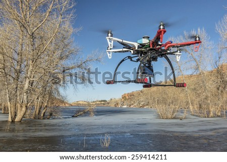 FORT COLLINS, CO, USA, March 9,  2015:  DJI F550 Flame Wheel  hexacopter drone is  flying with a camera over frozen lake. - stock photo