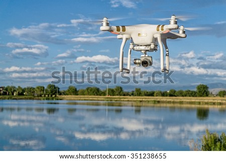 FORT COLLINS, CO, USA, SEPTEMBER 7 , 2015:  DJI  Phantom 3 quadcopter drone flying with a camera over a lake. - stock photo