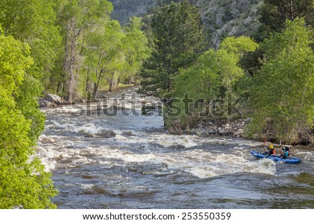 FORT COLLINS, COLORADO, USA - JUNE 4, 2011: Kayakers floating over Mad Dog Rapid on the Cache la Poudre River west of Fort Collins, Colorado as the snow pack in the high country begins to melt. - stock photo