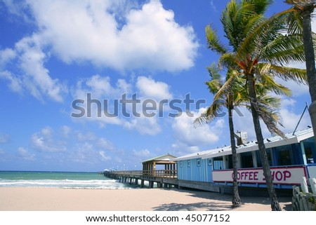 Fort Lauderdale beach cafe with tropical palm trees and blue sky - stock photo