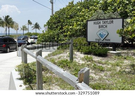 Fort Lauderdale, FL, USA - June 25, 2014: Beach front entry and sign to Hugh Taylor Birch State Park along A1A north of Sunrise Boulevard with beach, people, traffic on a sunny tropical day.