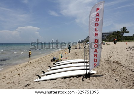 Fort Lauderdale, FL, USA - June 25, 2014: Five paddle boards for  rent on North Beach coast north of Sunrise Boulevard. There is a red and white banner sign on the beach next to the boards with people - stock photo