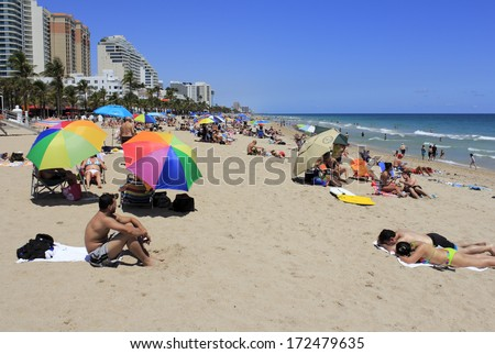 FORT LAUDERDALE, FLORIDA - APRIL 8, 2013: Colorful Atlantic coast beach scene of many people suntanning, relaxing and enjoying the shore during spring break on a hot and sunny, clear blue sky day.  - stock photo