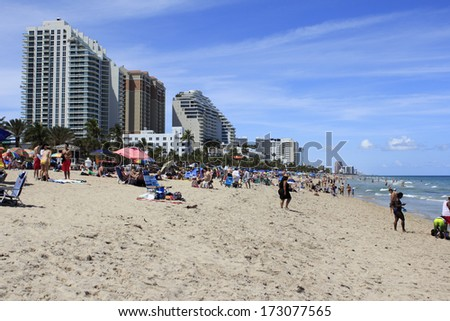 FORT LAUDERDALE, FLORIDA - APRIL 8, 2013: Long distance view of public beach filled with many people on spring break vacations, enjoying the warm sunny weather on the sand and in the Atlantic ocean. - stock photo