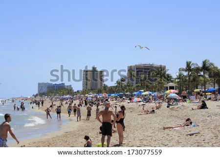 FORT LAUDERDALE, FLORIDA - APRIL 8, 2013: Very busy spring break day on the Atlantic coast beach with many people enjoying the hot and sunny tropical weather with many colorful umbrellas giving shade  - stock photo